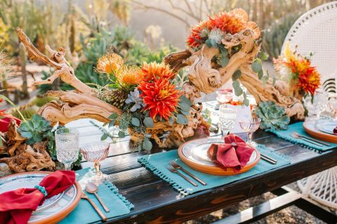 The centerpiece pulls in the southwestern decor of the setting. Burnt orange blooms and rich greenery pop against the textured wooden focal point.