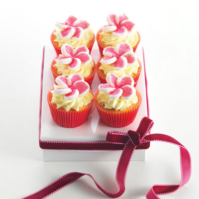 Fit a large piping bag with a large star tip, half-fill the bag with fluffy mock cream. Pipe stars on the top of each cake. Cut white marshmallows in half horizontally, dip the sticky side of each half in pink sugar sprinkles, pinch one end of each half to make a petal shape. Use five halves to make each flower, use some more sugar sprinkles to fill in any white gaps on the marshmallows.