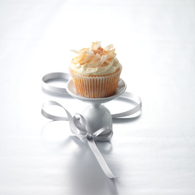 Stir coarsely flaked coconut in a frying pan over a low heat until it is browned lightly; remove from the pan immediately to cool. Spread the top of each cake generously with cream cheese frosting; sprinkle with the toasted coconut.