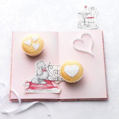 Use a hard plastic stencil that has varying sized and shaped hearts. Working with one cake at a time, place the stencil on the top of the cake, use a fine sifter to sift powdered sugar over the cut-out shapes. Gently lift the stencil off the cake. Brush the excess sugar from the stencil before using on the next cake.