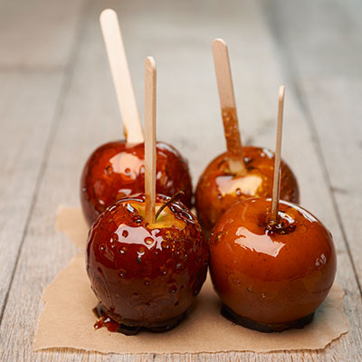 Once each apple is covered in caramel, place on a prepared piece of parchment paper, wax paper, or a baking sheet coated in nonstick cooking spray.