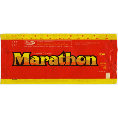 """Brand: Marathon Bar, Mars Year Launched: 1974 What Made It Great: Looped chocolate and caramel. """"Lasts a good long time"""" was the tagline for this braided, sticky, stretchable chocolate-covered caramel. The red and yellow packaging included a ruler measuring its super-sized 8-inch length. While Mars's Marathon Bar is long gone, Cadbury produces the Curly Wurly, a similar candy available in the U.K."""