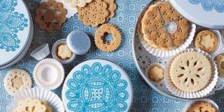 Use aspic cutters, essentially tiny cookie cutters, to create doily patterns. Recipe: Crisp Sugar Doily Cookies